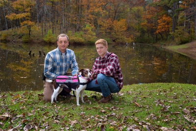 Steve and Riley Jones pose with Riley's dog, Sophie, in front of a pond.